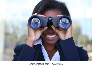 Beautiful african american business woman looking through binoculars