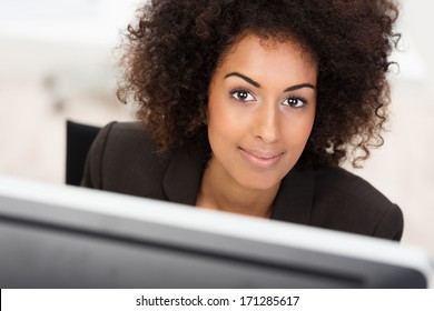 Beautiful African American businesswoman looking at the camera with a smile over the top of her computer monitor
