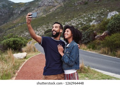 Beautiful african american couple taking selfie on their mobile phone cellphone on holiday roadtrip