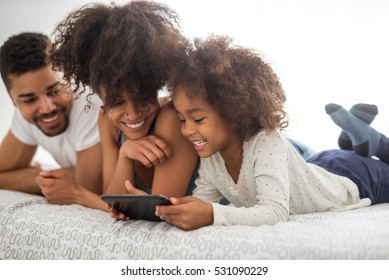 Beautiful african american family lying in bed and using tablet.