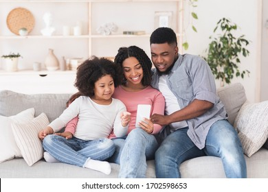 Beautiful african american family of three spending time with smartphone at home, watching videos or browsing internet, free space