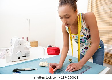 Beautiful african american fashion student drawing and cutting pattern on fabric with sewing machine, hand making clothes in home interior. Creative skills design, hobbies and lifestyle, black female.