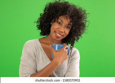 Beautiful African American female with coffee smiling at camera. Portrait of young woman holding coffee mug on green screen background