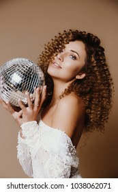 Beautiful african american girl with an afro hairstyle smiling.Hold disco ball,perfect brows and botox lips,french manicure ,emotional face,Presenting your product. Expressive facial expressions