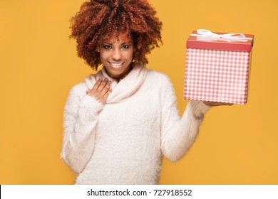 Beautiful african american girl with afro hairstyle holding gift box, smiling. Happy woman on yellow background.
