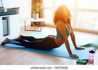 A beautiful African American girl doing yoga exercises on a yoga mat. She practices early in the morning at home, next to a large panoramic window. She does the exercises for the back.