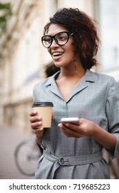 Beautiful African American girl in glasses standing on street with cellphone and coffee in hands while happily looking aside. Portrait of lady with dark curly hair in gray dress standing on street