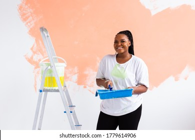 Beautiful african american girl painting the wall with paint roller. Portrait of a young beautiful woman painting wall in her new apartment. Redecoration and renovation concept.