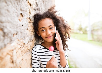 Beautiful african american girl with smart phone, eating lollipo