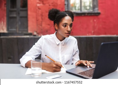 Beautiful African American girl in white shirt thoughtfully working with laptop in cozy courtyard of cafe