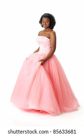 Beautiful African American Haitian teen girl wearing a pink strapless princess prom dress. Posing and smiling on a white background. Space for copy.