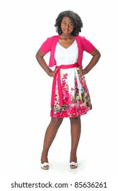Beautiful African American Haitian teen girl wearing a pink sweater and white and pink print dress, stands with her hands on her hips, smiling.  Photographed on a white background. Space for copy.