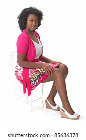 Beautiful African American Haitian teen girl wearing a pink and white dress and heels, sitting in a chair.  Photographed on a white background. Space for copy.