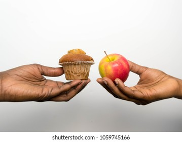 Beautiful African American hands holding a cup cake and an apple for diet struggle and confusion and decision for healthy eating and weight loss concept  nutrition choices dilemma