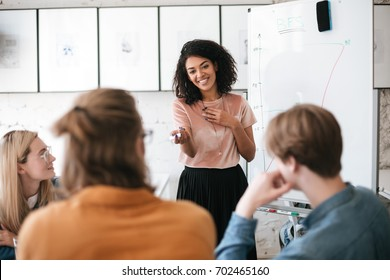 Beautiful African American lady with dark curly hair happily speaking about new project with her colleagues in office. Young smiling business woman giving presentation to coworkers