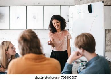 Linda senhora Africano americana com cabelo encaracolado escuro de pé perto do conselho e alegremente discutindo novo projeto com seus colegas no escritório. Mulher de negócios sorridente jovem dando apresentação aos colegas de trabalho