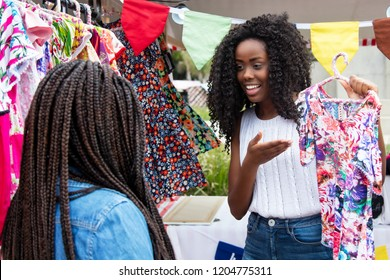 Beautiful african american market vendor presenting colorful clothes to customer at typical market