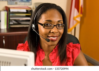 A beautiful African American receptionist wearing a headset and glasses smiling as she looks toward the camera