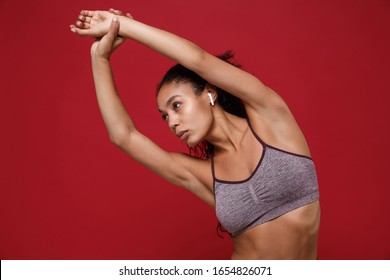 Beautiful african american sports fitness woman in sportswear working out isolated on red background. Sport exercises healthy lifestyle concept. Listen music with earpods, doing stretching exercising