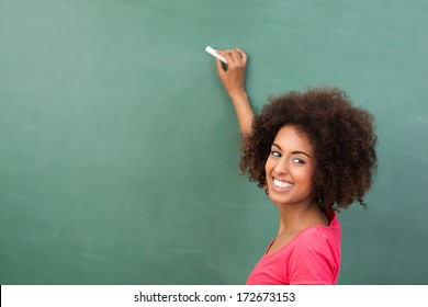 Beautiful African American student or teacher standing in front of the blank class blackboard with a piece of chalk in her hand ready to commence writing