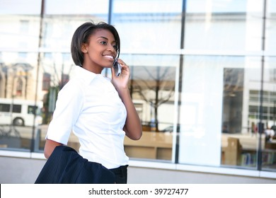 Beautiful african american student woman on the cell phone in front of library