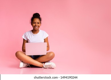 Beautiful african american teen sitting with laptop in lotus position on pink studio background
