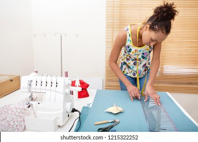 Beautiful african american teenager fashion student drawing and cutting pattern on fabric with sewing machine, hand making clothes in home interior. Creative skills design lifestyle, black female.