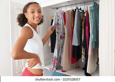 Beautiful african american teenager girl in home bedroom with open wardrobe selecting clothes, looking smiling in home interior. Healthy young woman with variety of garments, indoors, lifestyle.