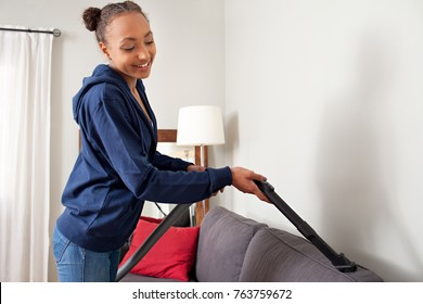 Beautiful african american teenager using vacuum cleaner on home sofa fabric, doing cleaning duties chores, smiling in living room interior. Young female working on house spring cleaning, interior.