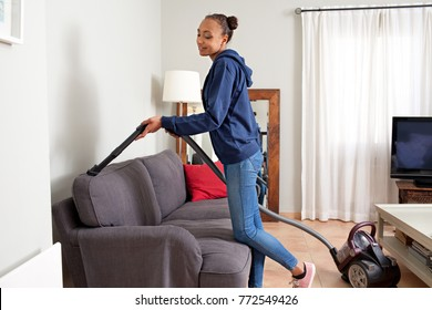Beautiful african american teenager using vaccum cleaner on home sofa fabric, enjoing cleaning duties chores, smiling in living room interior. Young female working on house spring cleaning, interior.