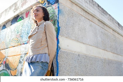 Beautiful african american teenager young woman leaning on graffiti wall in urban park, looking ahead, trendy and fashionable, sunny outdoors. Adolescent identity aspirational lifestyle, recreation.
