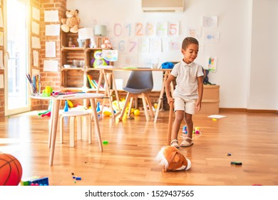 Beautiful african american toddler playing with horse toy with stick around lots of toys at kindergarten