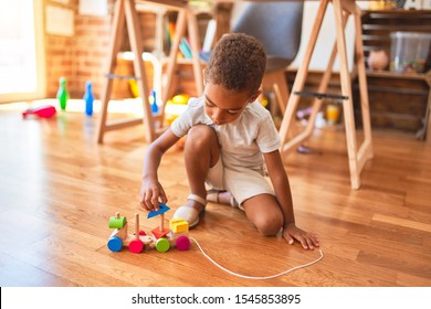 Beautiful african american toddler playing with wooden blocks train toy around lots of toys at kindergarten