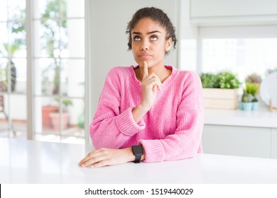 Beautiful african american woman with afro hair wearing casual pink sweater Thinking concentrated about doubt with finger on chin and looking up wondering