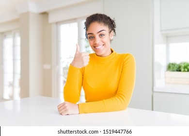 Beautiful african american woman with afro hair wearing a casual yellow sweater doing happy thumbs up gesture with hand. Approving expression looking at the camera showing success.