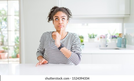 Beautiful african american woman with afro hair wearing casual striped sweater Thinking concentrated about doubt with finger on chin and looking up wondering