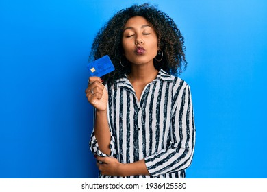 Beautiful african american woman with afro hair holding credit card looking at the camera blowing a kiss being lovely and sexy. love expression.
