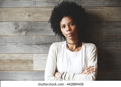 Beautiful African American woman with Afro hairstyle standing with folded arms against wooden copy space wall for your advertising content, looking at the camera with serious expression on her face