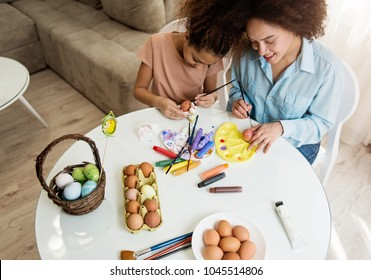 Beautiful African American woman and her daughter coloring Easter eggs at the table