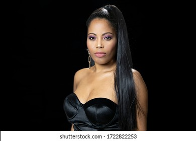 Beautiful African American woman in her twenties with long black straight hair posing in the studio on a black background