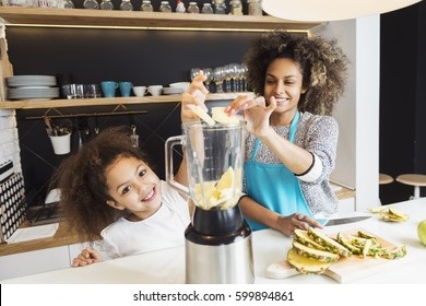 Beautiful African American woman and her daughter making a smoothie in the kitchen