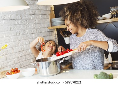 Beautiful African American woman and her daughter cooking in the kitchen