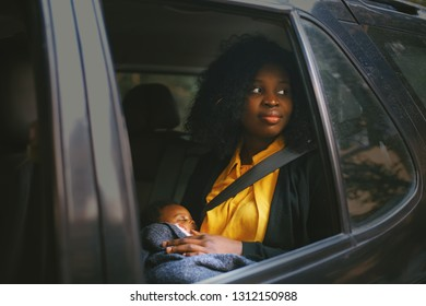 Beautiful african american woman holding a baby in a car back seat