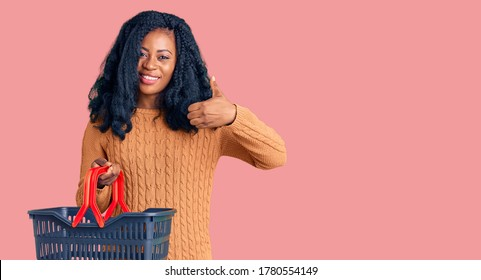 Beautiful african american woman holding supermarket shopping basket smiling happy and positive, thumb up doing excellent and approval sign