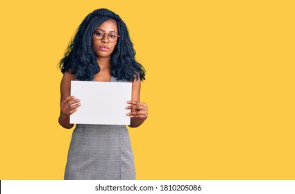 Beautiful african american woman holding blank empty banner thinking attitude and sober expression looking self confident