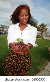 a beautiful african american woman holds a green plant in her hands