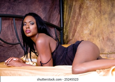 Beautiful African American Woman laying on a bed with gold sheets wearing black lingerie