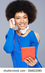 Beautiful African American woman listening to music downloaded on her tablet computer holding one of the earphones to her ear while smiling happily at the camera
