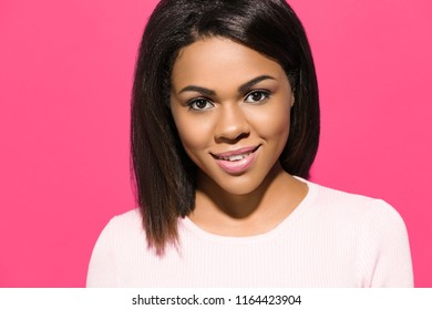 Beautiful African American woman is looking at camera and smiling, on pink background