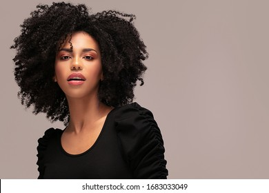 Beautiful african american woman looking at camera. Portrait of cheerful young woman with afro hairstyle. Beauty girl with curly hair.